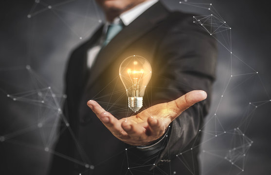 light bulb with businessman on his hand.