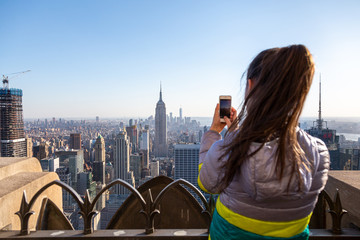 Tourist taking picture of New York City cityscape. Young woman looking at Manhattan panorama