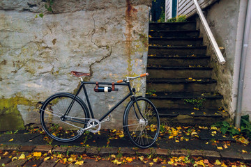 Bicycle with bottle of wine leaning on the old wall near the steps in Stavanger, Norway. Autumn