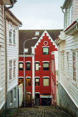 Red wall house in the middle of beautiful street with traditional white wooden houses in Stavanger, Norway. Summer