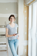 Happy confident young woman doing renovations