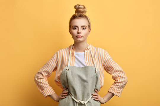 Young serious woman in apron posing with arms on hips and looking at the camera. close up photo. studio shot. housewife is ready to work. people, free time, hobby, spare time