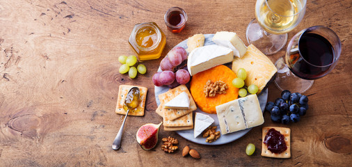 Assortment of cheese with red and white wine in glasses. Wooden background. Top view. Copy space.