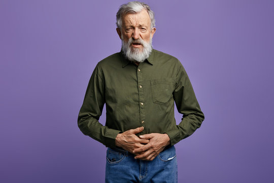 old man holds his stomach,looks at the camera with miserable expression.close up photo. isolated blue background, studio shot.