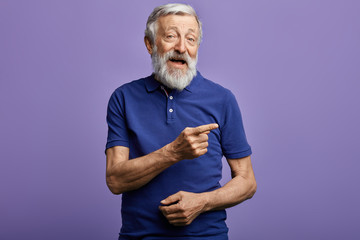 positive man pointing with hand and finger to the side. look here, happy old man showing direction,...