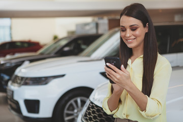 Cheerful beautiful woman smiling, typing messages on her smart phone while shopping for a new car at the dealership salon. Attractive female customer buying new automobile