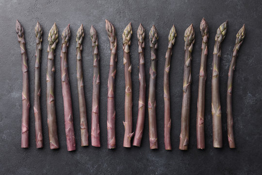 Fresh purple asparagus on textured black background, top view