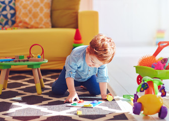 cute toddler baby boy playing with toys on the carpet at home