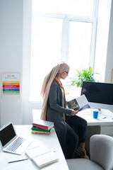 Teacher wearing hijab sitting near window and reading book