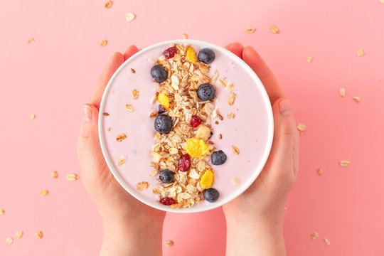 Woman's hands holding smoothie bowl on pink background. Top view, copy space.