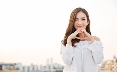 Portrait of young beautiful asian woman hands gesture in heart shape on city sky roof top. Smile face asian girl wear casual cloth. Japanese girl lifestyle, love valentines' day concept