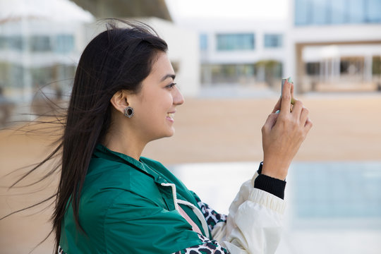 Side view of pretty young mixed-race woman in green jacket making photo on phone, smiling. Lifestyle concept