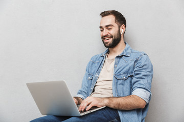 Photo of young laughing man having beard typing laptop and using earpod while sitting on chair