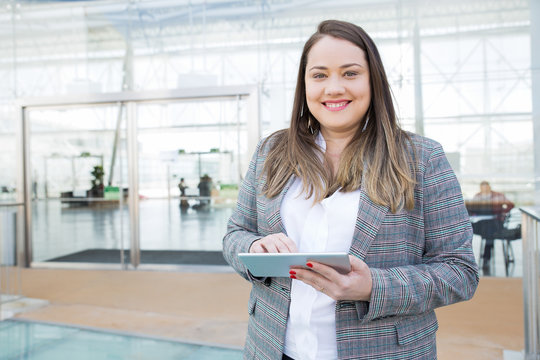 Positive lady with tablet posing in business center. Fat young woman in office jacket holding tablet and smiling at camera. Digital communication concept