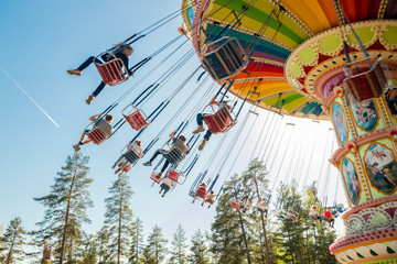 Fotobehang Amusementspark Kouvola, Finland - 18 May 2019: Ride Swing Carousel in motion in amusement park Tykkimaki and aircraft trail in sky.