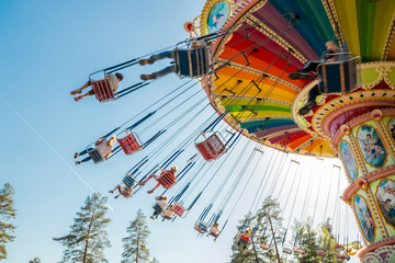 Kouvola, Finland - 18 May 2019: Ride Swing Carousel in motion in amusement park Tykkimaki and aircraft trail in sky. Fotobehang