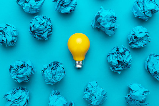 new idea concept with blue crumpled office paper and light bulb. top view of great business idea concept over blue background. creative solution during brainstorming session concept