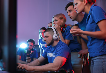 Young people playing video games on computers indoors. Esports tournament