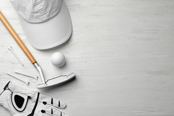 Flat lay composition with golf accessories and space for text on white wooden background