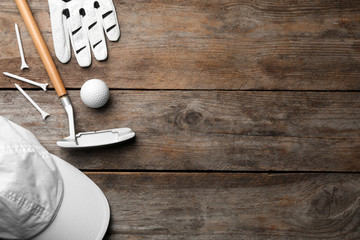 Flat lay composition with golf accessories and space for text on wooden background
