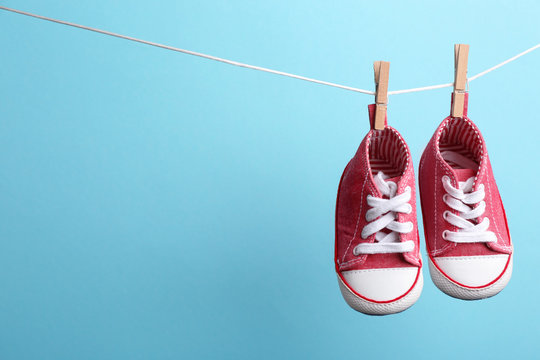 Cute small shoes hanging on washing line against color background, space for text. Baby accessories