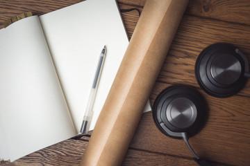 Fototapeta Czysty otwarty notes z długopisem leży na drewnianej podłodze, obok leżą słuchawki muzyczne. obraz
