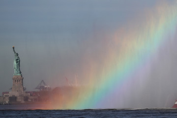 A rainbow is seen from the spray of a FDNY fireboat by the Statue of Liberty marking the beginning of Fleet Week in New York