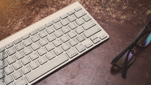 Wall mural  keyboard and glasses on wood table