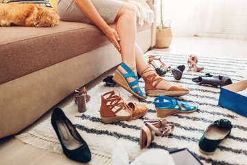 Woman choosing shoes and trying them on at home. Hard choice to make from sandals, heels and flats Wall mural