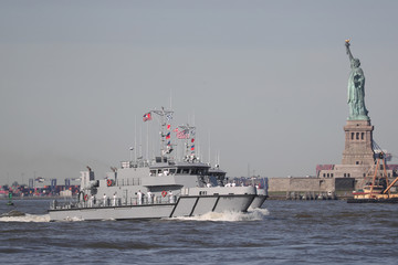 The U.S. Naval patrol craft makes its way past the Statue of Liberty in New York Harbor marking the beginning of Fleet Week in New York