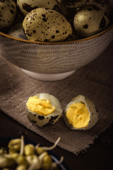 Quail eggs with mung bean sprouts in a bowl on dark wooden board
