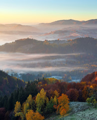 Wall Murals Deep brown Majestic autumn rural landscape. Interesting sunrise. A view from the lawn to the high mountains and forests in fog. Green meadows in frost. Picturesque resort Carpathians valley, Ukraine, Europe.