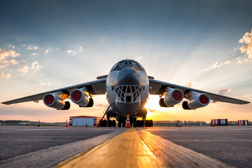 Wide body transport cargo aircraft at airport apron in the morning sun Wall mural