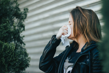 Young woman wearing a black leather jacket with a white tissue in her hand outside – Girl blowing her nose due to allergic reaction or virus infection – Concept image for allergy and having a flu