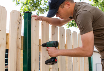 Young handsome man using electric cordless drill on wooden fence