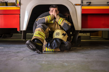 Picture of tired fireman sitting on floor near red fire truck