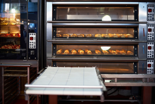 Industrial convection oven with cooked bakery products for catering. Professional kitchen equipment