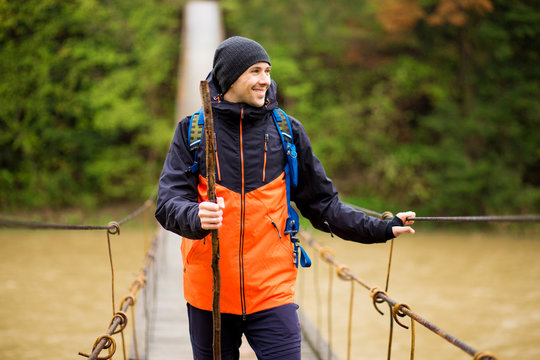 Man with backpack trekking in forest by hinged bridge over river. Cold weathe.