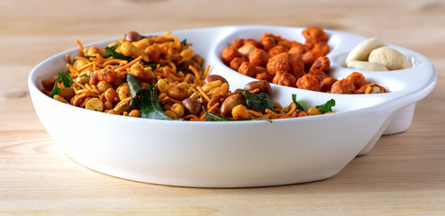 Assortment salty crunchy indian mix Nimco or Namkeen and spicy coated peanut white bowl wooden background.