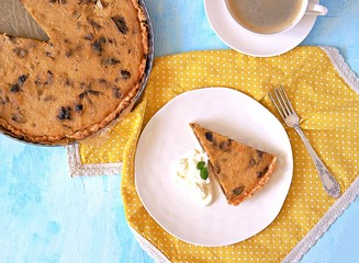 A portion of pumpkin pie with prunes on a white plate on a light blue background. Top view