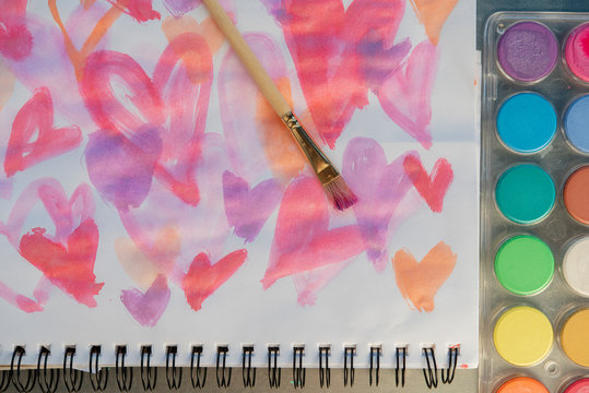 Paintbrush on watercolor painting of hearts by paints