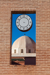 Dome behind brick window with clock in Marrakesh, Morocco