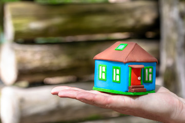 House miniature on palm on timber background. Abstract concept of building a new house