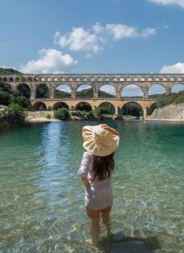 Woman wearing hat standing in Gardon River by Pont du Gard in Vers-Pont-du-Gard, France