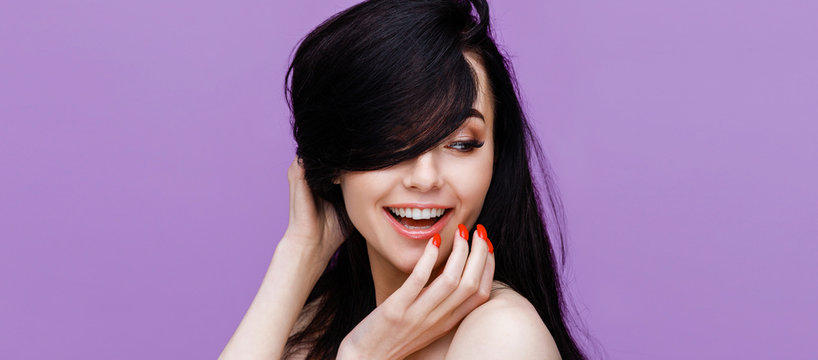 Beautiful smiling young woman with perfect glow clean skin touching her long shiny hair. Portrait of happy model with make up, red manicure and bare shoulders on purple background.