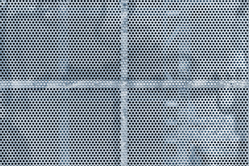 Close up of the gray colored metal background with the holes.