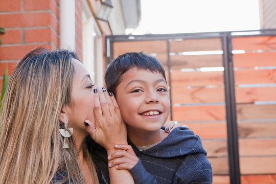 Mother whispering into her son's ear