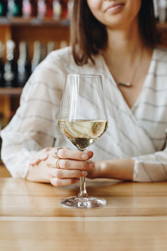 Woman holding glass of white wine