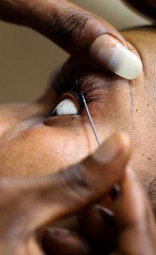 A woman gets fake eyelashes in beauty salon in Abidjan