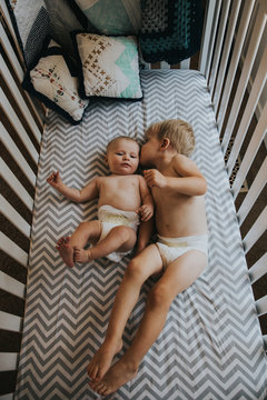 Toddler boy giving baby brother a kiss while laying in crib